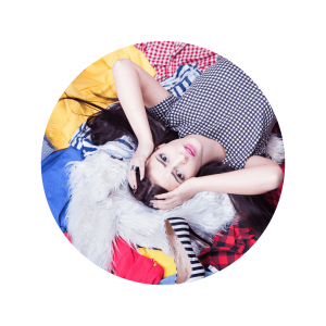 Woman lying on a pile of clothes holding her head
